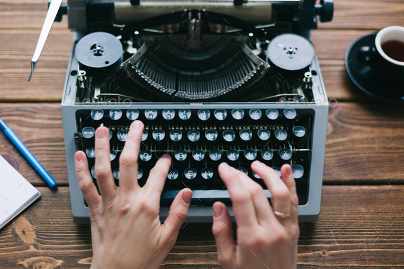 Crop person using typewriter - Stock Photo - Images