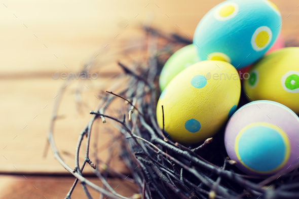 close up of colored easter eggs in nest on wood - Stock Photo - Images