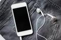 smartphone and earphones on denim or jeans pocket