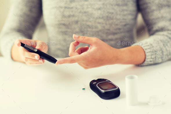 close up of woman making blood test by glucometer - Stock Photo - Images