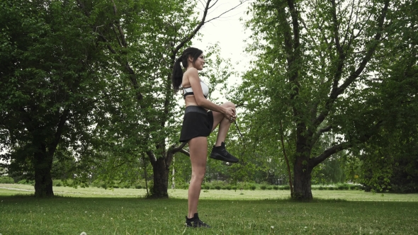 20s Sporty Female Warms Up and Starts Running on the Park. Girl Athlete Running Summer Forest