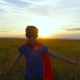 A Boy in a Superman Costume Runs Across the Green Field at Sunset