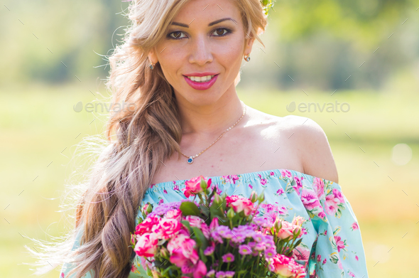 Close-up portrait of beautiful blonde girl holding bouquet of flowers at the countryside - Stock Photo - Images