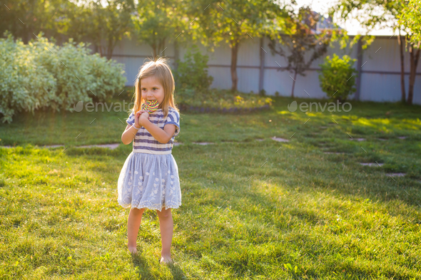 cute cauasian baby girl and big lollipop - Stock Photo - Images