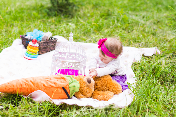 Cute little happy baby girl with big brown teddy bear on green grass meadow, spring or summer season - Stock Photo - Images