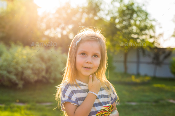 cute little girl eating a lollipop on the grass in summertime. - Stock Photo - Images