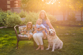 Happy mother and two children with Golden Retriever dog in the garden.