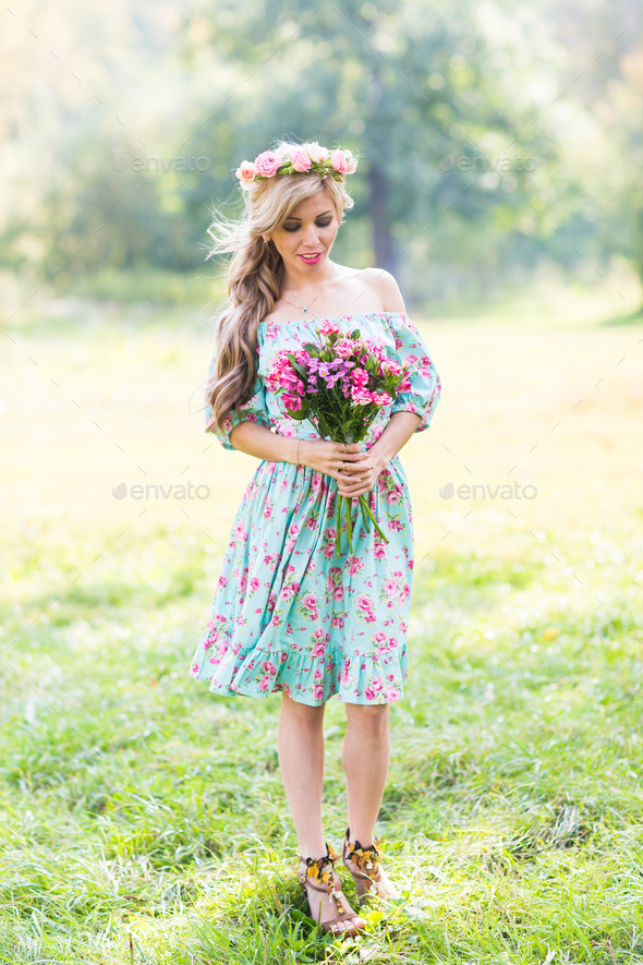 Beautiful blonde girl holding bouquet of flowers at the countryside - Stock Photo - Images