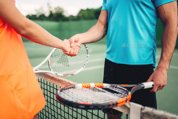Man and woman partners on outdoor tennis court - Stock Photo - Images