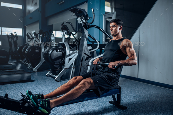 Muscular man workout on exercise machine - Stock Photo - Images