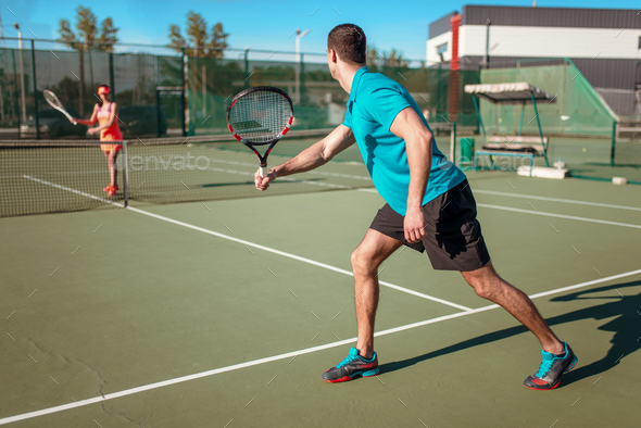Couple playing tennis on outdoor court - Stock Photo - Images
