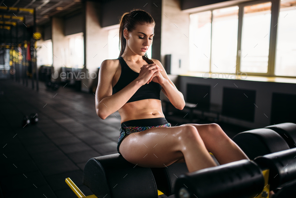 Slim female athlete trains press in sport gym - Stock Photo - Images