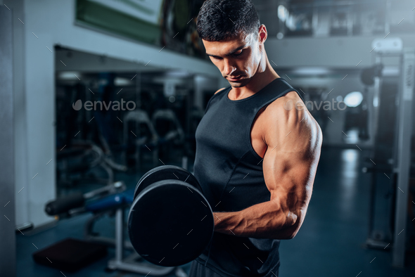 Tanned muscular athlete workout with dumbbell - Stock Photo - Images