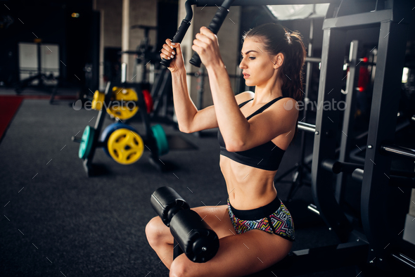 Female athlete trains on exercise machine in gym - Stock Photo - Images