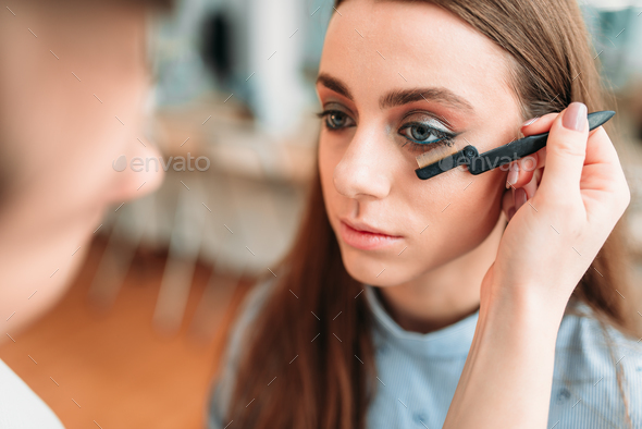 Makeup artist work with woman eyelashes - Stock Photo - Images
