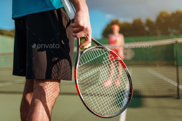Male and female person playing tennis outdoor - Stock Photo - Images