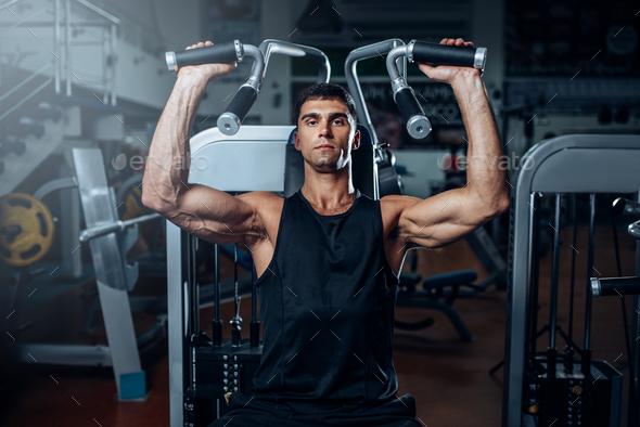 Tanned man training on exercise machine - Stock Photo - Images