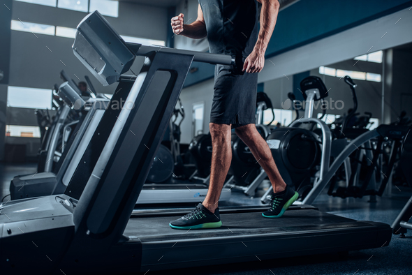 Male person workout on running exercise machine - Stock Photo - Images