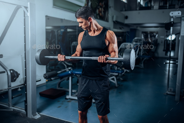 Tanned muscular man workout with barbell in gym - Stock Photo - Images
