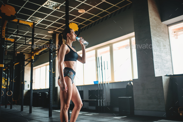 Female athlete drink water after training in gym - Stock Photo - Images