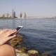 Young Woman Using Smartphone Sitting on Embankment Near the Sea and Skyscrapers of Megapolis - VideoHive Item for Sale