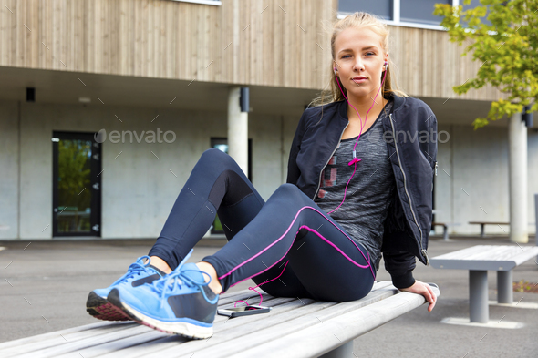 Confident Woman In Sportswear Listening Music On Bench - Stock Photo - Images