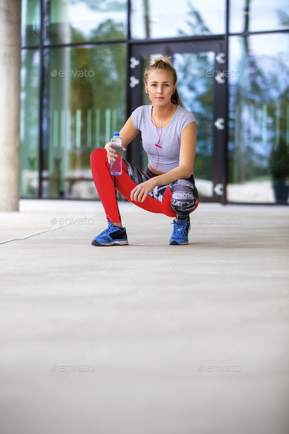 Sporty Woman Holding Water Bottle While Crouching On Footpath - Stock Photo - Images
