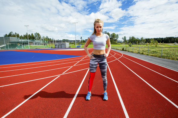 Sporty Female Standing With Hands On Hips On Running Tracks - Stock Photo - Images