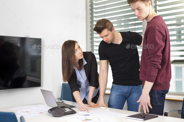 Businesswoman Explaining Plan To Coworkers At Desk - Stock Photo - Images