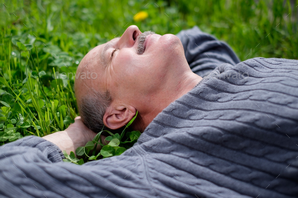 Mature Happy Man Lying On Green Grass. He holds onion leaf in mouth and closes eyes. - Stock Photo - Images