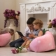 Little Girl With Brother Plays With The Tablet In a Convenient Chair.
