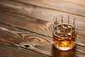 Glass of whiskey with ice cubes on wooden table - PhotoDune Item for Sale
