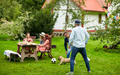 friends playing football with dog at summer garden