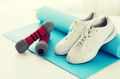 close up of sneakers, dumbbells and sports mat