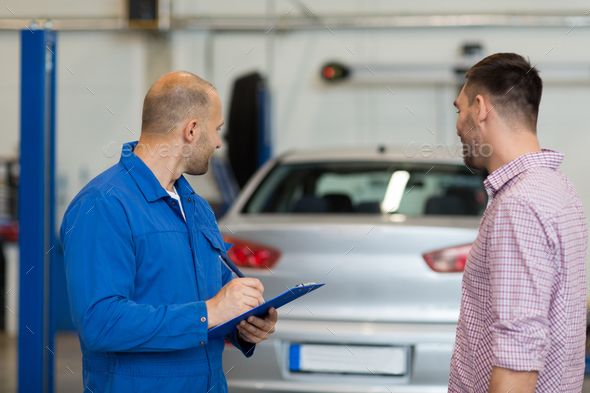 auto mechanic with clipboard and man at car shop - Stock Photo - Images