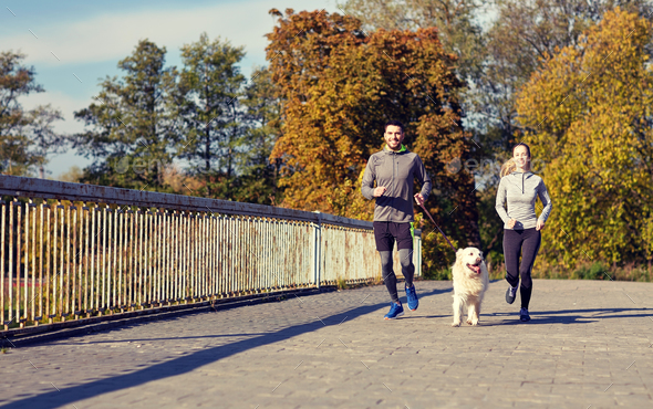 happy couple with dog running outdoors - Stock Photo - Images