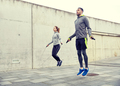man and woman exercising with jump-rope outdoors