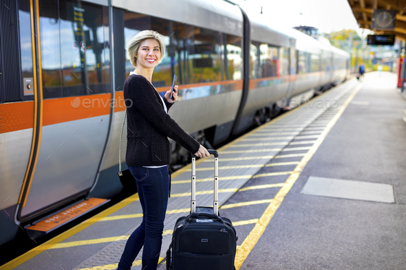 Happy Woman With Mobile Phone And Luggage At Train Station - Stock Photo - Images