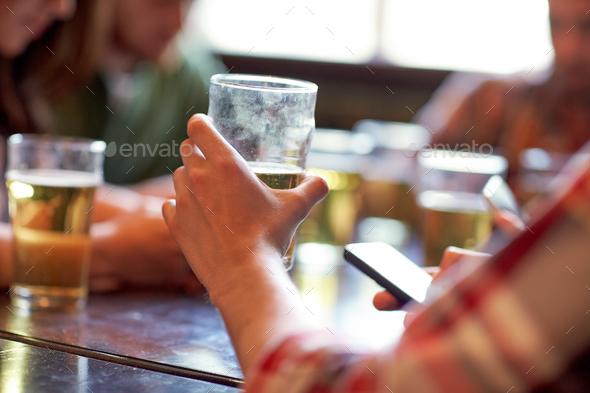 man with beer and smartphones at bar or pub - Stock Photo - Images