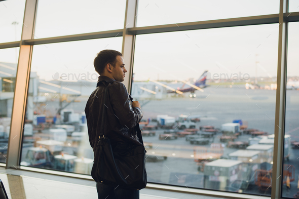 Travel concept with young man in airport interior with city view and a plane flying by. - Stock Photo - Images