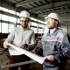 Foreman and Chief Engineer at the Construction Site of the Factory. The Engineer Checks the Drawing