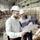 Architect and Chief Foreman at the Construction Site of the Plant. Men Discuss Drawbacks in the