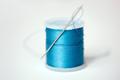 red thread spool on cloth