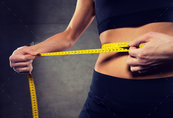 close up of woman measuring waist by tape in gym - Stock Photo - Images