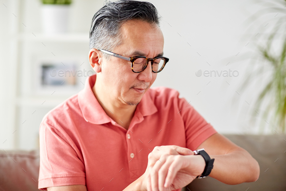 asian man checking time on wristwatch at home - Stock Photo - Images