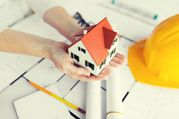 close up of hands with house model above blueprint - Stock Photo - Images