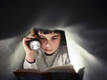 Young Boy School Child Reading Book At Night Under Covers