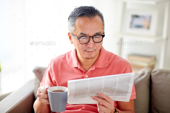 man drinking tea and reading newspaper at home - Stock Photo - Images