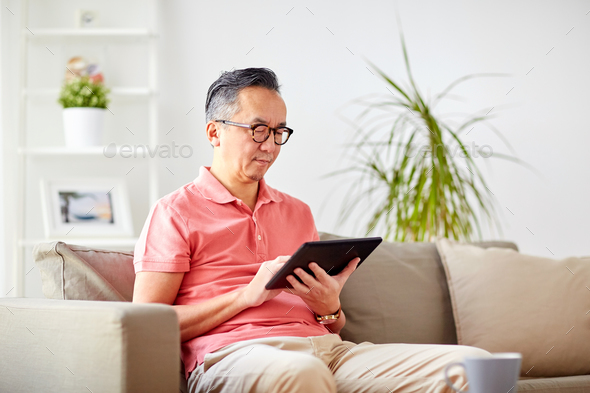 man with tablet pc sitting on sofa at home - Stock Photo - Images