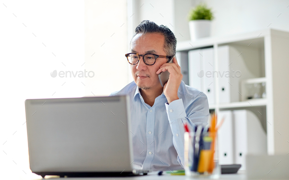 businessman with laptop calling on smartphone - Stock Photo - Images